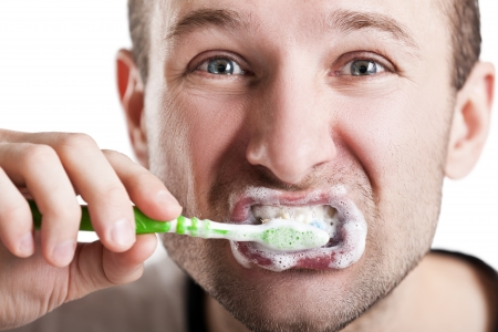 Dental hygiene - man holding toothbrush with toothpaste in hand and brushing teeth