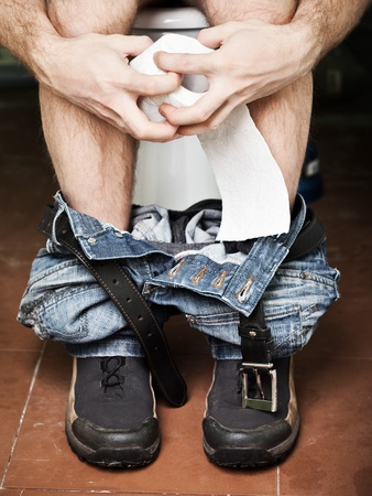 Adult man sitting on bathroom or wc toilet bowl holding paper in hands and making poo photo