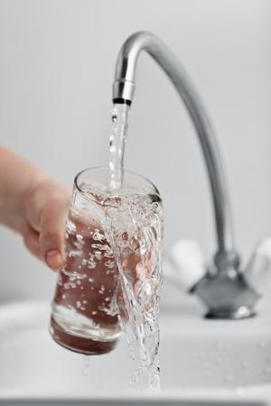 agua grifo: La mano del hombre de vidrio de verter el agua bebida fresca en el grifo de la cocina