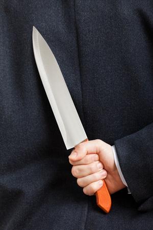 holding a knife: Murderer human hand holding sharp steel kitchen knife weapon