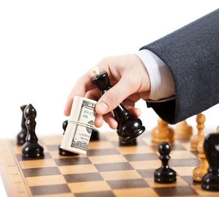 chess board: Business man hand holding dollar currency unfair playing chess game