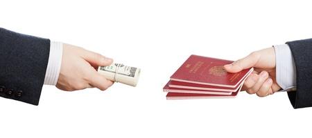 dinero falso: La mano del hombre de negocios la celebraci�n de enrollado de papel moneda del d�lar para la compra de documento de identidad falso pasaporte o falsificados Foto de archivo