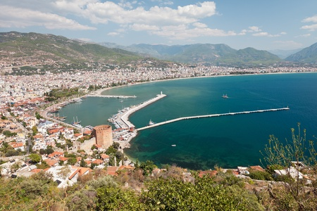 Summer vacations - blue Mediterranean sea and Turkey Alanya east coast beach resort with lighthouse and ship bay view from ancient mountain castle wall photo