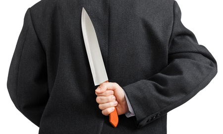 hidden danger: Murderer human hand holding sharp steel kitchen knife weapon