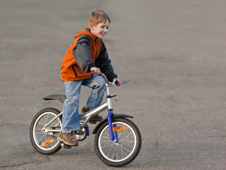 Little smiling child boy cycling sport bicycle outdoor
