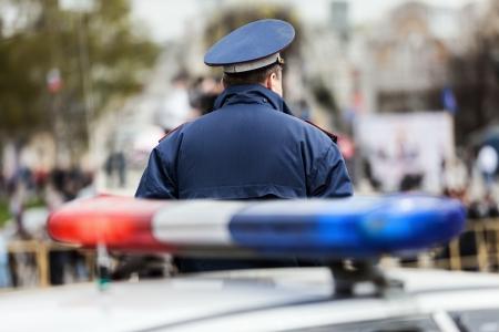 Crime Gesetz Sicherheitsdienst Offizier Polizist bewachte Straße in der Nähe Polizeiauto mit Sirene Licht