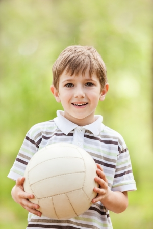 Little smiling child boy playing soccer sport ball outdoor photo