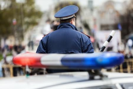 Security-Dienst Offizier Polizist mit Schlagstock Verkehr Bewachung Straße in der Nähe Polizeiauto mit Sirene Licht