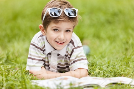 Beauty smiling child boy in sunglasses reading book outdoor on green grass field Stock Photo - 14000340