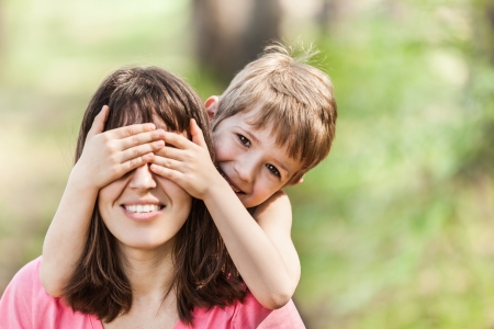 covering eyes: Smiling mother and little son - family happiness Stock Photo