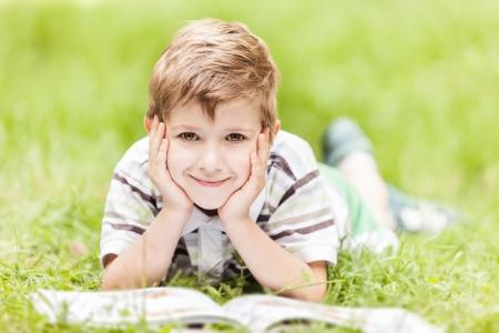 Beauty smiling child boy reading book outdoor on green grass field Standard-Bild