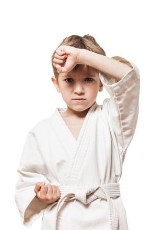 El deporte de artes marciales - ni�o chico en blanco kimono de formaci�n golpe de karate photo