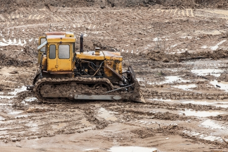 contruction: Old rusty earth digging caterpillar bulldozer machine working at building construction site Stock Photo