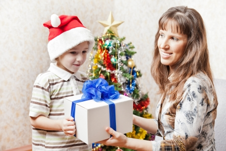 Smiling mother giving new year present or christmas holiday gift box to little son wearing Santa Claus hat photo