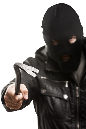 Crime scene - criminal thief or burglar man in balaclava or mask covering face holding crowbar in hand for break opening home door lock Stock Photo