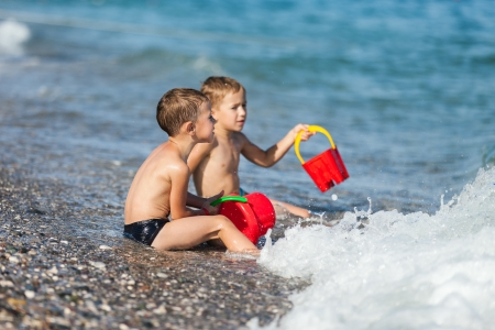 kids playing beach: Summer vacations - two little child boy brothers playing on blue sea sand beach Stock Photo