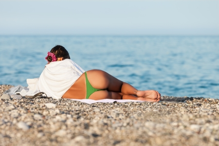Summer vacations - beauty woman with slim legs and buttocks on sea beach