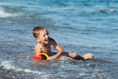 Summer vacations - little smiling child boy playing on sea sand beach photo