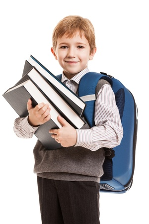 school age boy: Little smiling child boy with school backpack holding education books in hands