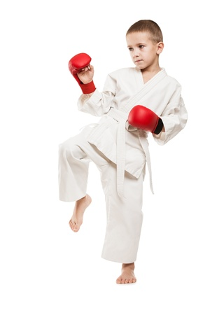 Martial art sport - child boy in white kimono training karate punch or kick photo