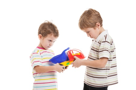 Two little displeased child boy brothers fighting for toy in family conflict