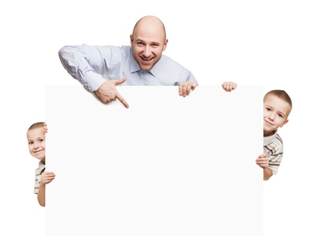 indicating: Smiling father and little sons holding blank sign or placard white isolated