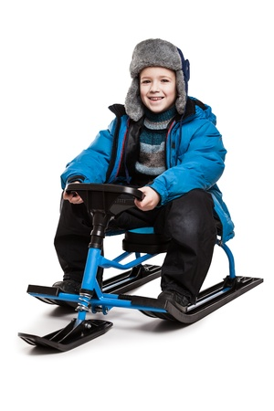 to steer a sledge: Little smiling child boy sitting on snow scooter or snowmobile toy white isolated