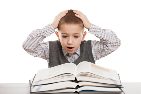 Amazed or surprised child boy reading education books at desk photo