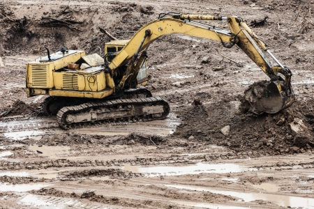 Old rusty earth digging excavator machine working at building construction site Stock Photo - 17693692