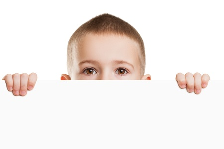 Little scared or worried child boy holding blank white sign or placard hiding face photo