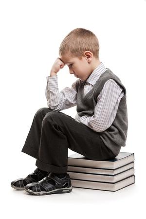 pensador: Chico pensador niño desconcertado o perplejo sentado leyendo libros pila de educación Foto de archivo