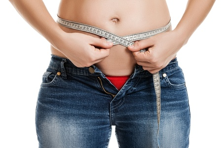 paunch: Overweight woman wearing jeans measuring her fat body belly paunch