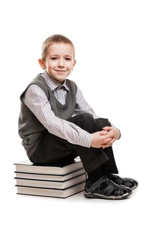 Little smiling child boy sitting on education reading books stack