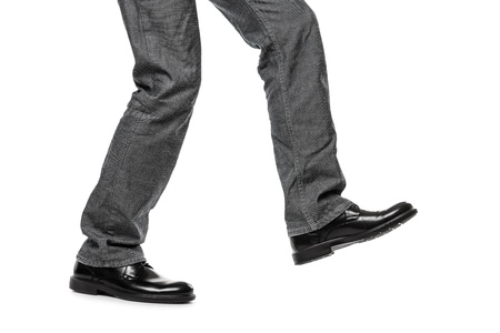 move forward: Business man in black shoes walking for next achievement or promotion step white isolated