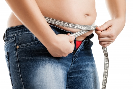 potbelly: Overweight woman wearing jeans measuring her fat body belly paunch