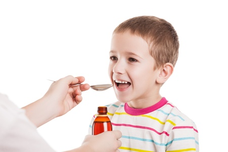 Doctor hand giving spoon dose of medicine liquid drinking syrup to child boy patient photo