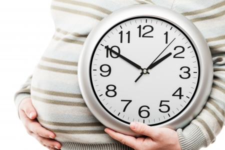 Pregnancy and new life concept - beauty pregnant woman hand holding large office wall clock showing time Standard-Bild