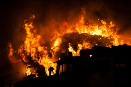 Arson or nature disaster - burning fire flame on wooden house roof