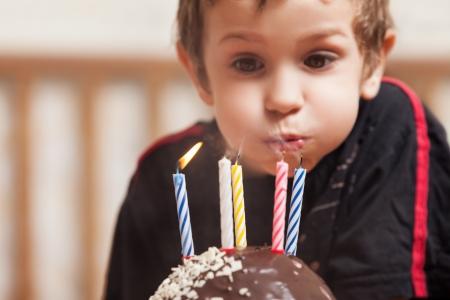 torta con candeline: Piccolo bambino sorridente che soffia dolce festa di compleanno del fuoco candela