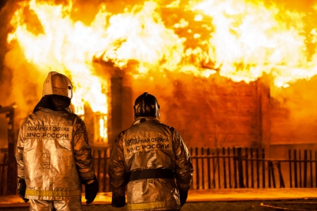 Arson or nature disaster - firefighters at burning fire flame on wooden house roof