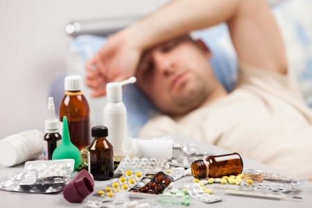 resfriado: Hombre paciente adulto con altas temperaturas que se acuesta cama para alivio de una enfermedad de resfriados y gripe