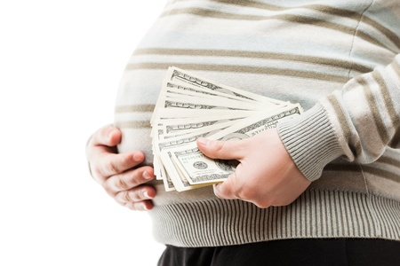Pregnancy and surrogacy concept - pregnant woman hand holding dollar currency cash