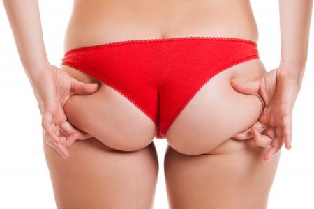 nalga: Sobrepeso Mujer mano que sostiene o pellizcar inferior de grasa corporal o las nalgas blancas aisladas retrovisor Foto de archivo
