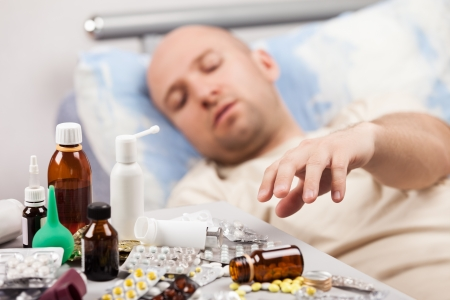 bronchitis: Adult man patient with high temperature lying down bed for cold and flu illness relief Stock Photo