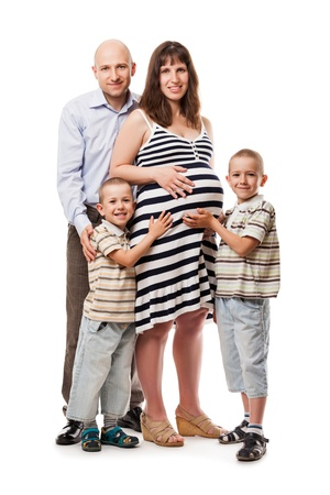 Pregnancy and new life concept - father and two little sons touching or bonding pregnant mother abdomen photo