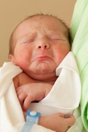 Loving mother hand holding cute sleeping newborn baby child photo