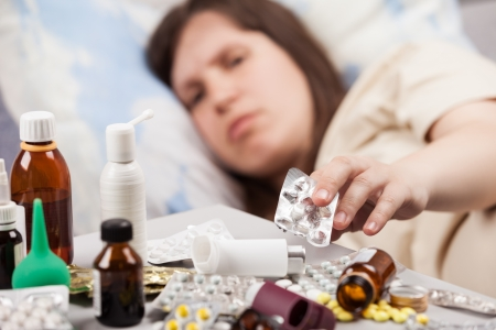 Adult woman patient hand holding vitamin pills lying down bed for cold and flu illness relief Stockfoto