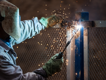 Heavy industry welder worker in protective mask hand holding arc welding torch working on metal construction photo
