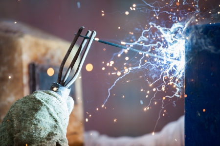 Heavy industry welder worker in protective mask hand holding arc welding torch working on metal construction Stock Photo - 21948174