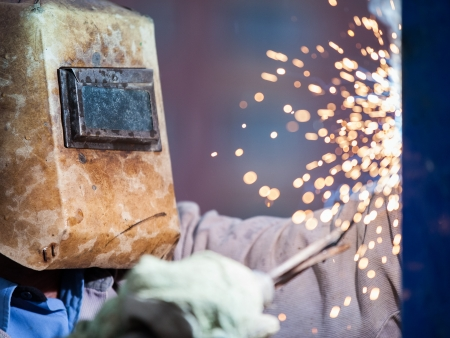 machinist: Heavy industry welder worker in protective mask hand holding arc welding torch working on metal construction